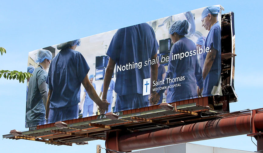 Picture of doctors and nurses and other healthcare professionals in prayer circle - billboard from Saint Thomas Health traditional and digital healthcare marketing campaign Nashville TN
